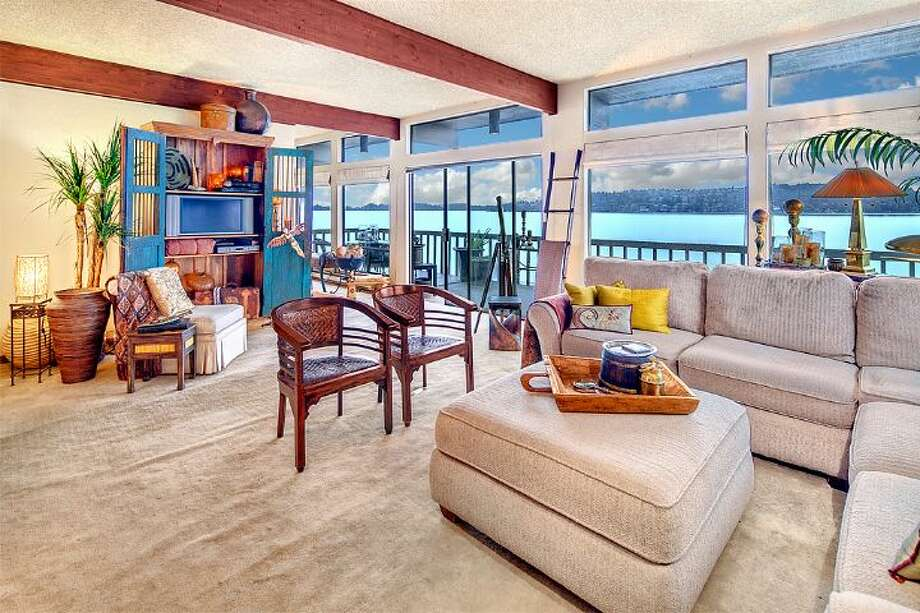 Living room of 9860 Rainier Ave. S. The 2,601-square-foot house, built in 1971, has four bedrooms, two bathrooms, exposed wood beams, a covered, dock-level entertaining area, a sauna, decks, views and a two-car garage on a 1,213-square-foot lot with 50 feet of frontage along Lake Washington. It's listed for $650,000. Photo: Courtesy Bryan Loveless And Richard Eastern/Windermere Real Estate