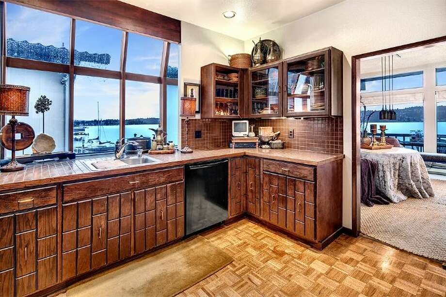 Kitchen of 9860 Rainier Ave. S. The 2,601-square-foot house, built in 1971, has four bedrooms, two bathrooms, exposed wood beams, a covered, dock-level entertaining area, a sauna, decks, views and a two-car garage on a 1,213-square-foot lot with 50 feet of frontage along Lake Washington. It's listed for $650,000. Photo: Courtesy Bryan Loveless And Richard Eastern/Windermere Real Estate