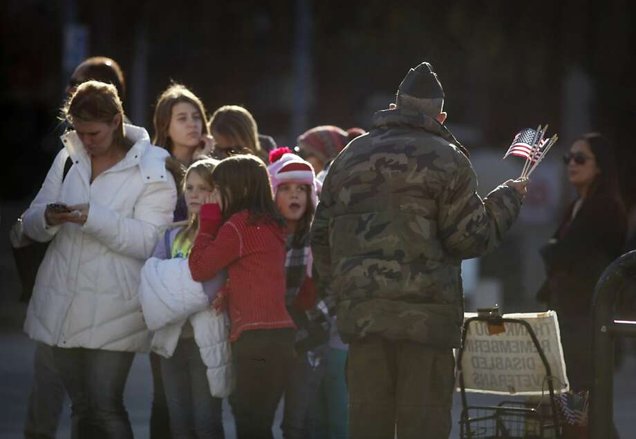 A group of children and other pedestrians watch as disabled Vet Philip Myers holds a bouquet of American flags in front of the Ferry Plaza. Photo: Mike Kepka, The Chronicle