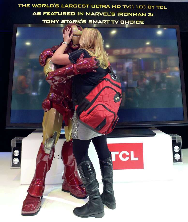 A woman kisses Iron Man at the TCL booth  at the 2013 International CES on Thursday. Photo: JOE KLAMAR, AFP/Getty Images / AFP