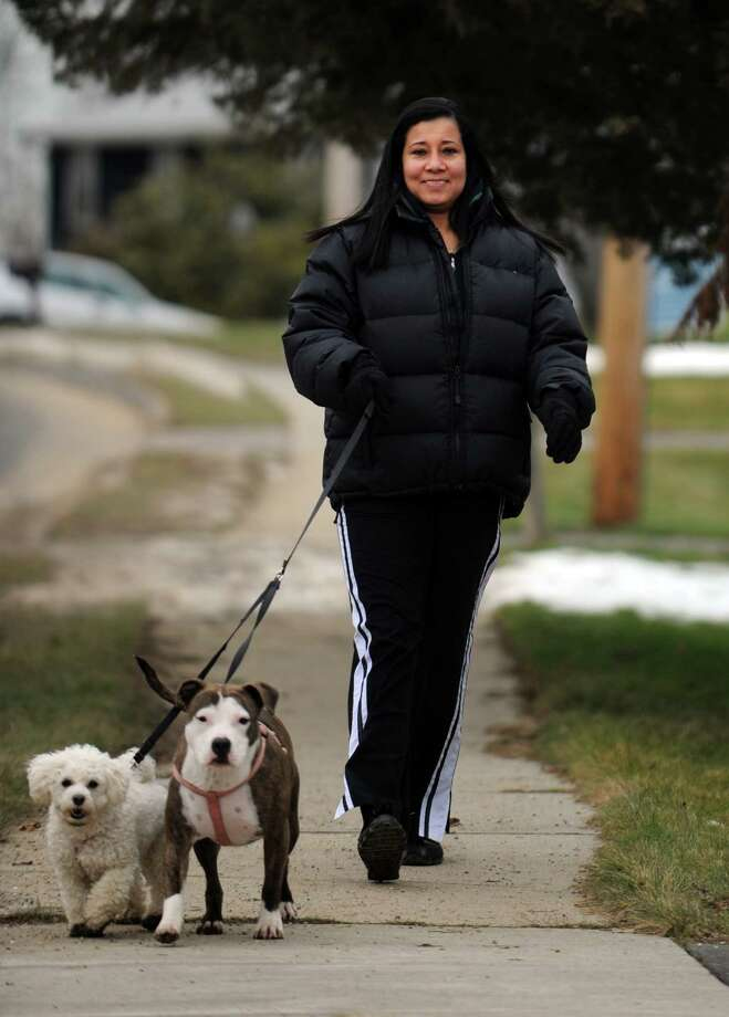 Nelsy Londono walks her dogs, Minnie, left, and Nala, Friday, Jan. 11, 2013 near her home in Ansonia, Conn. Photo: Autumn Driscoll / Connecticut Post