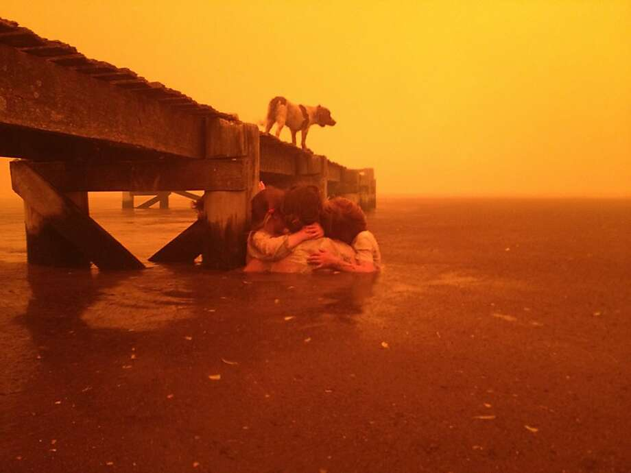 Australia's record-setting summer temperatures have sparked hundreds of wildfires across the southeast section of the country. Fires stormed through the Tasmanian town of Dunalley, Australia, where Tammy Holmes and her grandchildren took refuge under a jetty. Photo: Tim Holmes, Associated Press