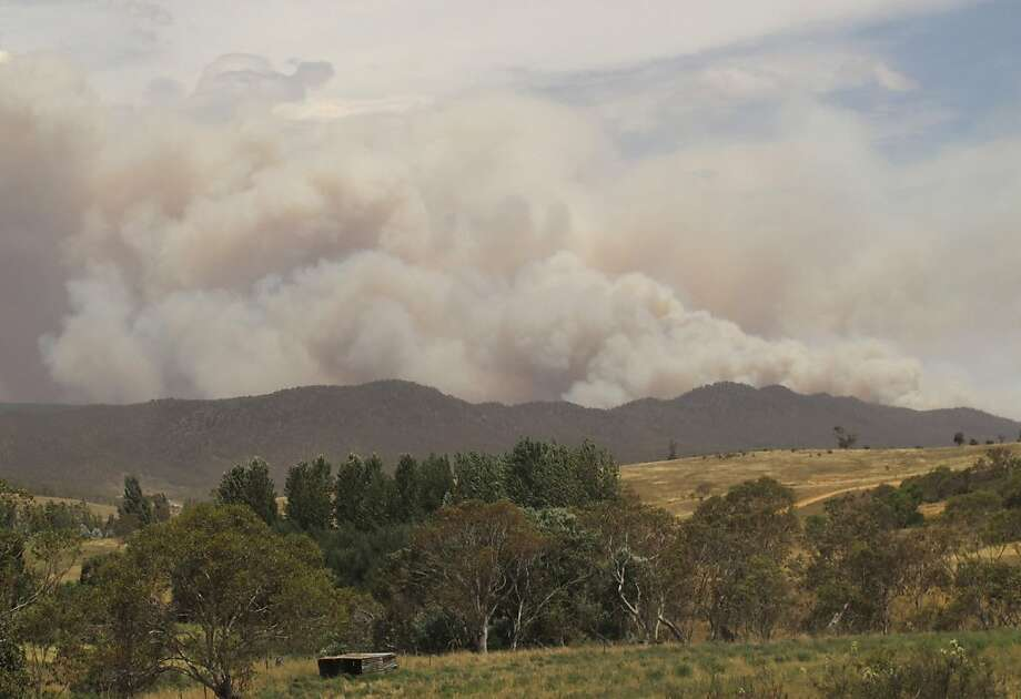 Smoke rises from the hills near the village of Numeralla in New South Wales. Photo: Rod McGuirk, Associated Press