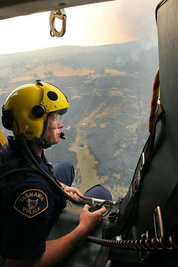 Westpac Police rescue helicopter crewman, Sgt. Matthew Drumm, surveys the fire near Dunalley. Photo: Chris Kidd, Associated Press