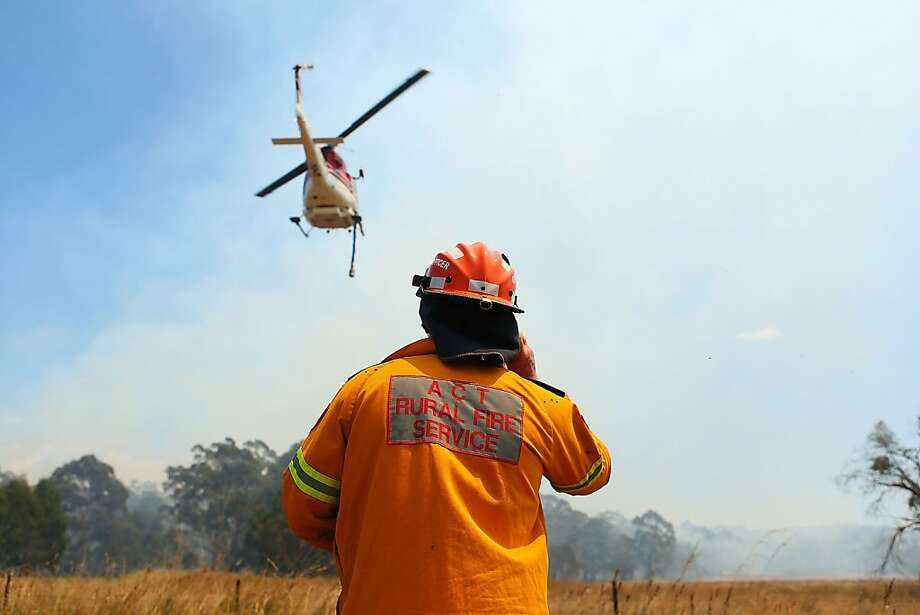 A ACT Rural Fire Service member keeps watch over water-bombing operations on a fire at Sandhills in Bungendore, Australia. Photo: Brendon Thorne, Getty Images