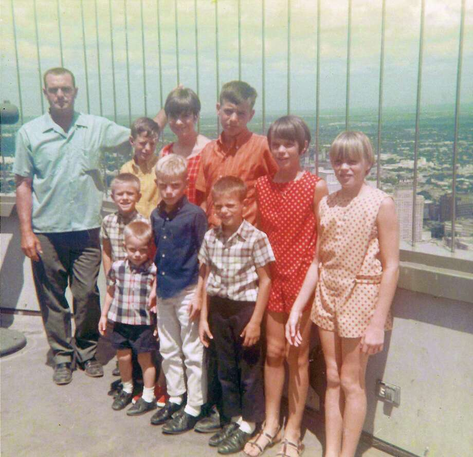 Then: In 1968 Rene and Rosie Aelvoet from Hondo visited HemisFair with their nine children. While on the observation deck at the top of the Tower of the Americas, Rosie took this photo of Rene and the kids. They are, back row, from left, Rene, Andrew, Annette, Frank, Mariette and Jeanette. Front row,  Patrick, David, Paul and Tommy. Photo: Rosie Aelvoet, Courtesy Photo