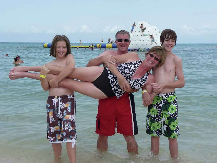 Then:During a family cruise in 2008, the Scott boys, Braden, 14, and Garrett, 13, engage in a little horseplay with their dad David and mom Mandy on the beach in Cozumel. Photo: Courtesy Photo, Mandy Scott, Reader Submission