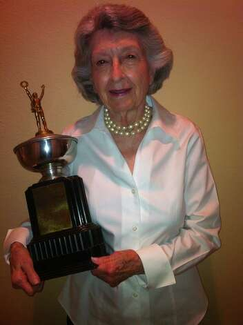 "In 1946, Frances Perl won a trophy reading ""1946 Memorial Award presented by Brownsville Lions Club for Outstanding Achievements to Frances Perl."" Sixty-six years later she again poses with the trophy.