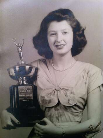 "Frances Perl Goodman holds a trophy reading, ""1946 Memorial Award presented by Brownsville Lions Club for Outstanding Achievements to Frances Perl.""