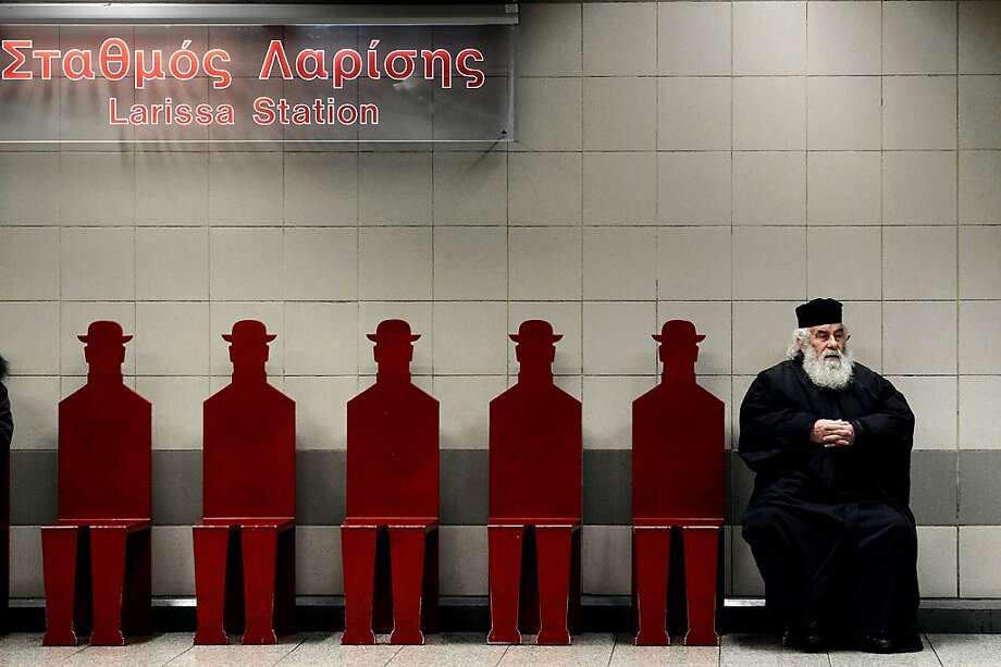 Greek Orthodox priest sits on a platform at the Athens' Larissa metro station on January 11, 2013.  Photo: Aris Messinis, AFP/Getty Images