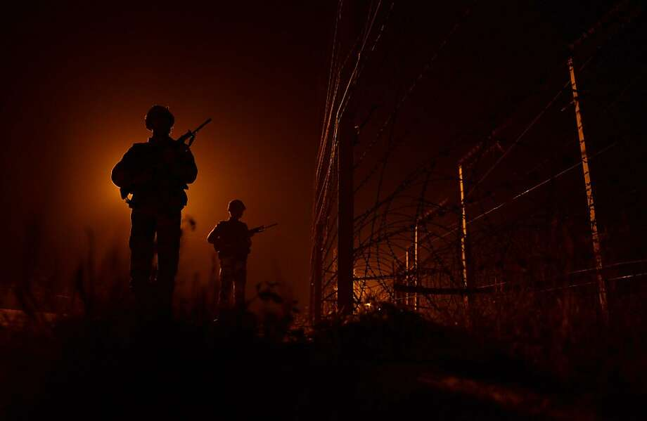 "Tension at the border: Indian security force soldiers patrol the fence at an outpost along the India-Pakistan border in Suchit-Garh. Pakistan summoned the Indian ambassador to protest ""unacceptable and unprovoked"" attacks by the Indian army that left two Pakistani soldiers dead in Kashmir. Photo: Tauseef Mustafa, AFP/Getty Images"