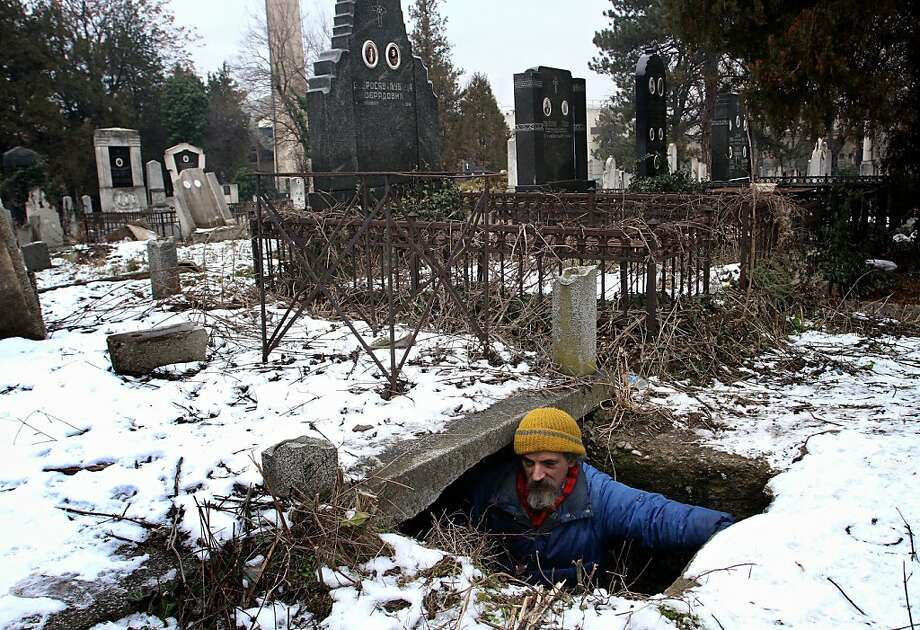 """On the bright side, the neighbors are quiet:Bratislav Jovanovic enters his """"house"""" - a tomb beside the caskets of his descendants in the Serbian city of Nis. Jovanovic, 43, has been homeless since his house burned down nearly 20 years ago. He uses the grave for shelter in the winter. Photo: Sasa Djordjevic, AFP/Getty Images"""