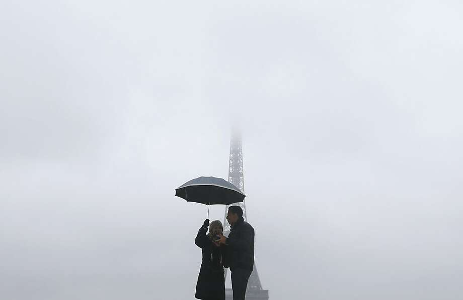 Maybe we should kiss instead of just holding this umbrella? A couple pose for a romantic Eiffel Tower-in-the-fog photo in Paris' Trocadero Square. Photo: Kenzo Tribouillard, AFP/Getty Images