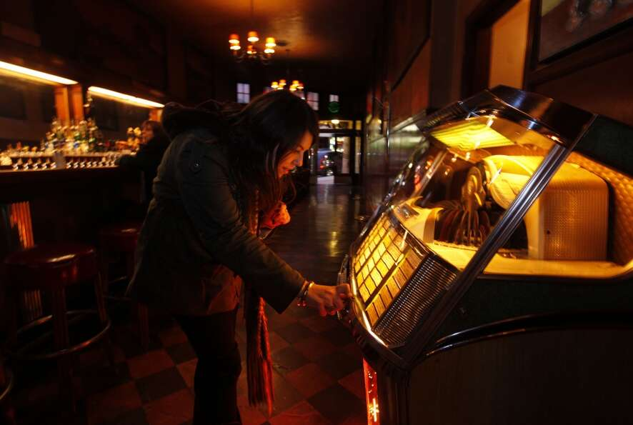 Devin Mantalto picks out songs to play on the juke box at historic Tosca Cafe on Wednesday Jan. 9,