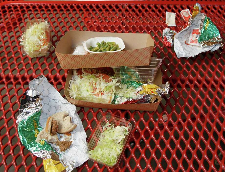 FILE - This Jan. 17, 2012, file photo shows vegetables left over by students on their cafeteria trays at the Roosevelt High School in Los Angeles. Americans blame too much screen time and cheap fast-food for fueling the nation's obesity epidemic, but a poll finds that they're split on how the government should help. A third of people say the government should be deeply involved in finding ways to curb obesity. A similar proportion want the government to play little or no role, and the rest are in the middle. (AP Photo/Damian Dovarganes, File) Photo: Damian Dovarganes