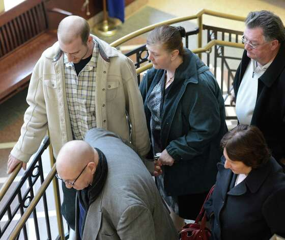 LuAnn Burgess, center, surrounded by family members, leaves the Albany County Courthouse after her sentencing by Judge Stephen Herrick Friday morning, Jan. 11, 2013 in Albany, N.Y.   Burgess pled guilty to three counts of criminally negligent homicide and agreed to never drive again.    (Skip Dickstein/Times Union) Photo: SKIP DICKSTEIN / 00020706A
