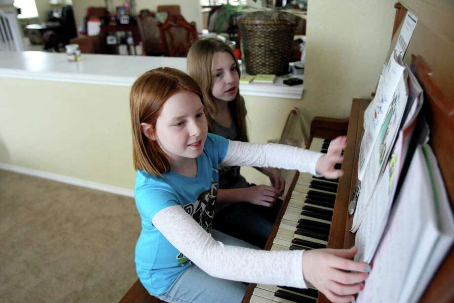 Tana Lux, 7, gets help with her piano lesson from sister Tori Lux, 12. Photo: Helen L. Montoya, Staff / ©SAN ANTONIO EXPRESS-NEWS