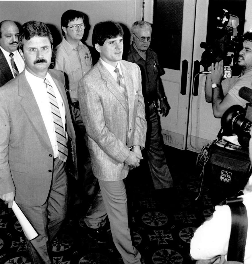 Michael Lee Lockhart, middle right in suit, enters a courtroom in San Antonio Tuesday morning followed by media. Escorting him is Ken Dollinger, the witness co-ordinator for Jefferson County Texas. He killed officer Paul Hulsey