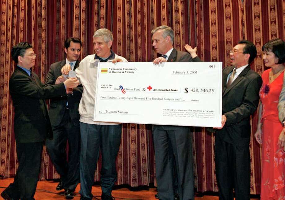 Jay Guerrero, a representative from Sen. John Cornyn's office, joins Jim McIngvale and Red Cross chairman Thomas Standish presenting a check for more than $428,000 for tsunami victims. Related story. Photo: Craig H. Hartley, . / freelance