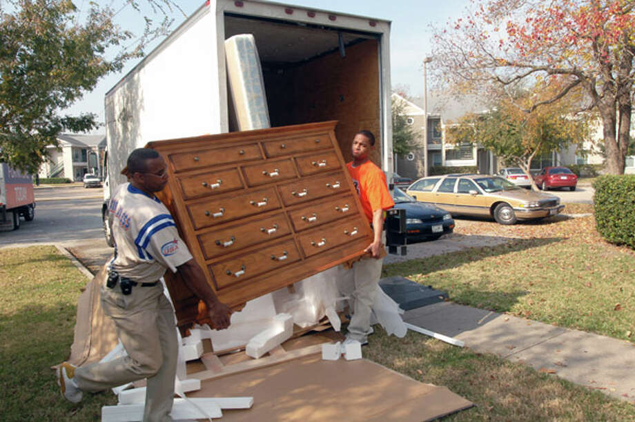 Rufus Bonner and Kevin Williams deliver furniture to a winner of the Christmas Give Away sponsored by Gallery Furniture. Related story. Photo: Eddy Matchette, . / Freelance