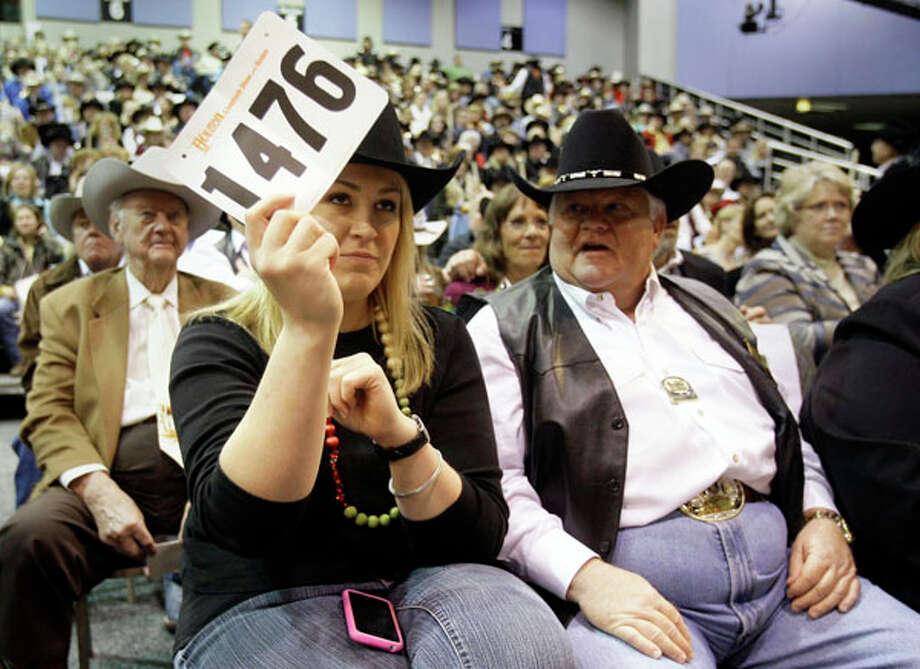 Laura McIngvale daughter of  Jim McIngvale owner of Gallery Furniture's,  bids on the Grand Champion during the  Junior Market  Steer Auction at Reliant Arena Sales Pavilion at the Houston Livestock Show and Rodeo Saturday, March 14, 2009, in Houston. She said family friend Dr. Philip Leggett, shown right, helped talk her through the bidding process. She won the bidding at $300,000 against Dick Wallrath of Champion Ranch who stopped at $275,000. The bid ties last year price. The record price of $600,001 was set in 2002. Photo: Melissa Phillip, . / Houston Chronicle