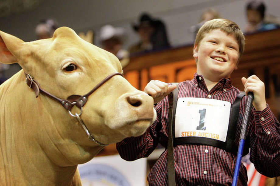 Chris Barton of Jarrell with his Grand Champion after the final bid during the  Junior Market  Steer Auction at Reliant Arena Sales Pavilion at the Houston Livestock Show and Rodeo on March 14, 2009.  Laura McIngvale won the bidding at $300,000. Related story. Photo: Melissa Phillip, . / Houston Chronicle