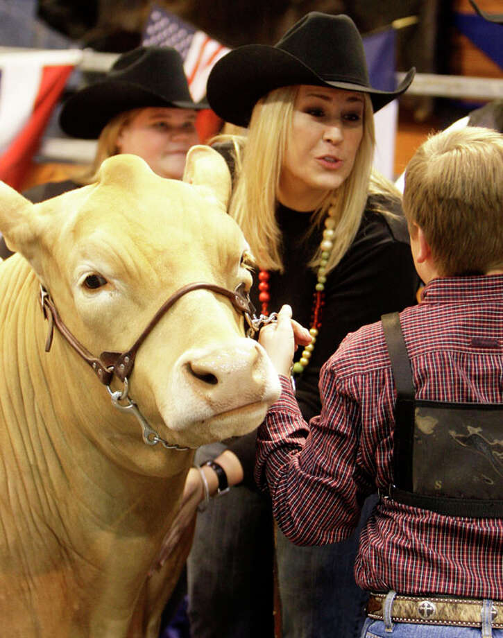 Laura McIngvale daughter  of Jim McIngvale owner of Gallery Furniture's,  talks with Chris Barton of Jarrell after she on the bid on his Grand Champion during the  Junior Market  Steer Auction at Reliant Arena Sales Pavilion at the Houston Livestock Show and Rodeo Saturday, March 14, 2009, in Houston. She won the bidding at $300,000 against Dick Wallrath of Champion Ranch who stopped at $275,000. The bid ties last year price. The record price of $600,001 was set in 2002. Photo: Melissa Phillip, . / Houston Chronicle