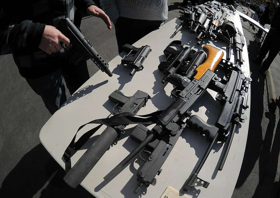 An LAPD officer stands before collected assault weapons during the LAPD Gun Buyback Program event  in the Van Nuys area of north Los Angeles,  on December 26, 2012.  Los Angeles' no-questions-asked gun buyback event, where weapons could be exchanged for up to $200, was held five months early after the Connecticut school shooting.   Gun owners could take their arms to one of two locations in return for a $100 grocery store gift card for handguns, rifles and shotguns, or a $200 card for automatic weapons. AFP PHOTO / JOE KLAMARJOE KLAMAR/AFP/Getty Images Photo: Joe Klamar, AFP/Getty Images