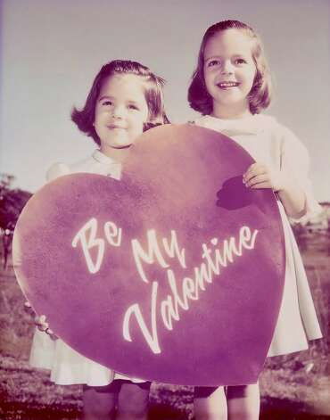 Then: On Valentine  Day 1965 the Sunday Express and News ran a color photo in the Family section of Marcia Myers, 5, and her sister Melinda, 3 holding a large red Valentine heart.  My sister and I have very distinct and vivid memories of the [newspaper] photographer coming to our home to shoot the picture   at one point he had us standing on the trunk of our car to get the shot,  writes Marcia. Photo: Marcia Myers, Reader Submission