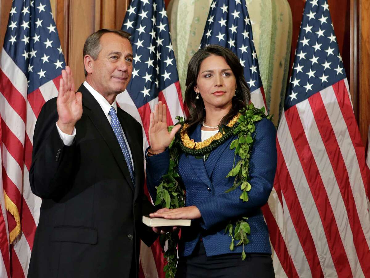 U.S. Rep. Tulsi Gabbard, D-Hawaii, stands for a ceremonial photo with Speaker of the House John Boehner, R-Ohio, in the Rayburn Room of the Capitol.