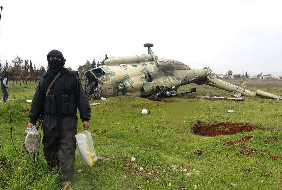 A Syrian rebel carries food near a damaged helicopter at Taftanaz air base, the largest air base to be captured by the rebels, in a citizen journalism image provided by Edlib News Network. Photo: Anonymous, Associated Press