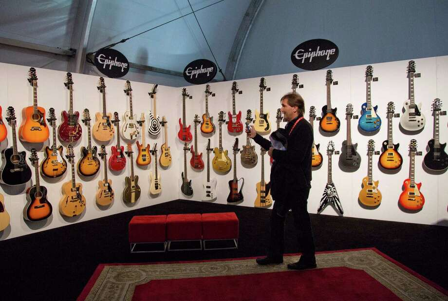 A convention attendee browses through a display of Epiphone electric guitars. Photo: Julie Jacobson, Associated Press / AP
