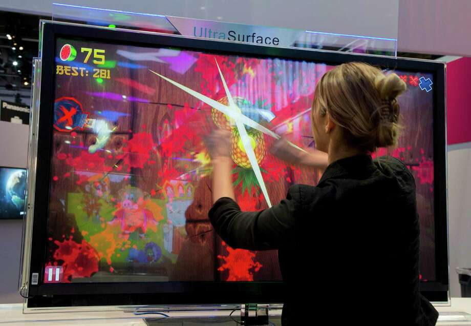 An attendee plays Fruit Ninja at the Panasonic booth. Photo: Julie Jacobson, Associated Press / AP