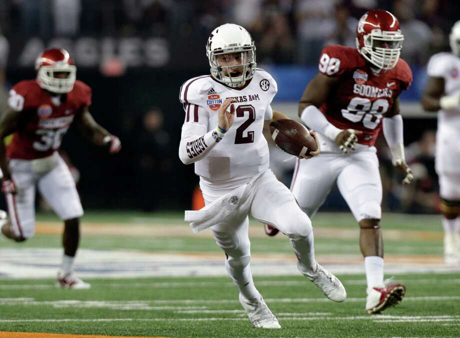 Texas A&M's Johnny Manziel (2) finds running room as Oklahoma's Javon Harris (30) and Chuka Ndulue (98) give chase in the first half of the Cotton Bowl NCAA college football game Friday, Jan. 4, 2013, in Arlington, Texas. (AP Photo/LM Otero) Photo: LM Otero, Associated Press / AP