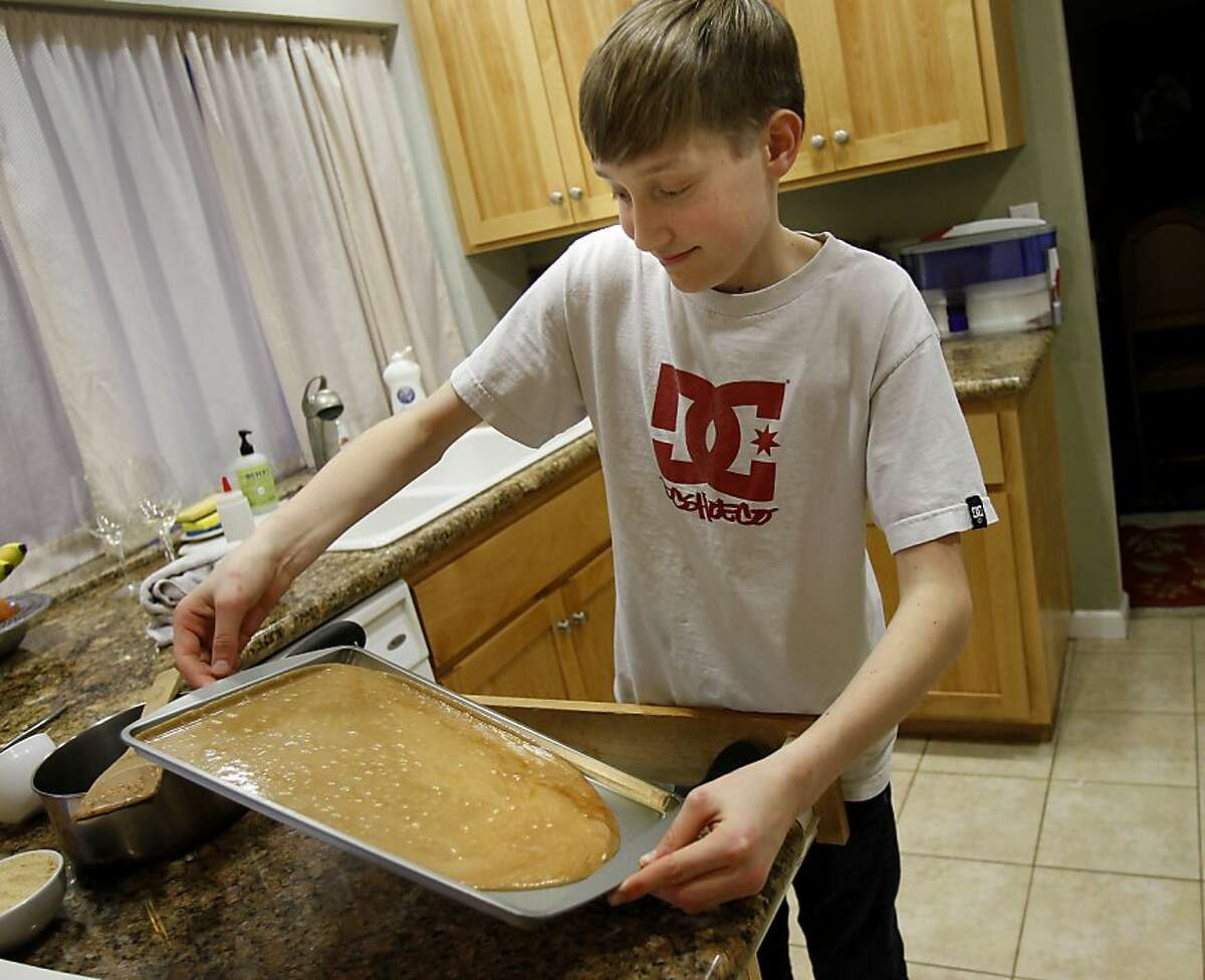Tucker Fish spreads his toffee mixture around a baking sheet in his kitchen at home. Thirteen year old Tucker Fish of Santa Rosa, Calif. has invented a candy bar that he plans to sell to raise money for college and possible scholarships for others. He is using crowd funding through Kickstarter to fund his project with some help from his parents.