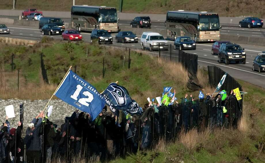 As the team's buses (background) approach, hundreds of Seahawks fans erupt in cheers during a sendoff rally for the Seattle Seahawks in Renton on Friday, January 11, 2013. A crowd of hundreds gathered on an Interstate 405 overpass and cheered the team as their buses headed to the airport for the trip to Atlanta and Sunday's playoff game. Photo: JOSHUA TRUJILLO / SEATTLEPI.COM