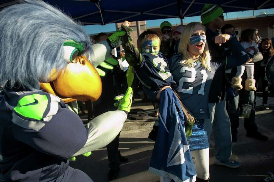 Brittany Zinter-Miller and Kelly, 3, show their spirit along with Seahawks mascot Blitz during a sendoff rally for the Seattle Seahawks in Renton on Friday, January 11, 2013. A crowd of hundreds gathered on an Interstate 405 overpass and cheered the team as their buses headed to the airport for the trip to Atlanta and Sunday's playoff game. Photo: JOSHUA TRUJILLO / SEATTLEPI.COM