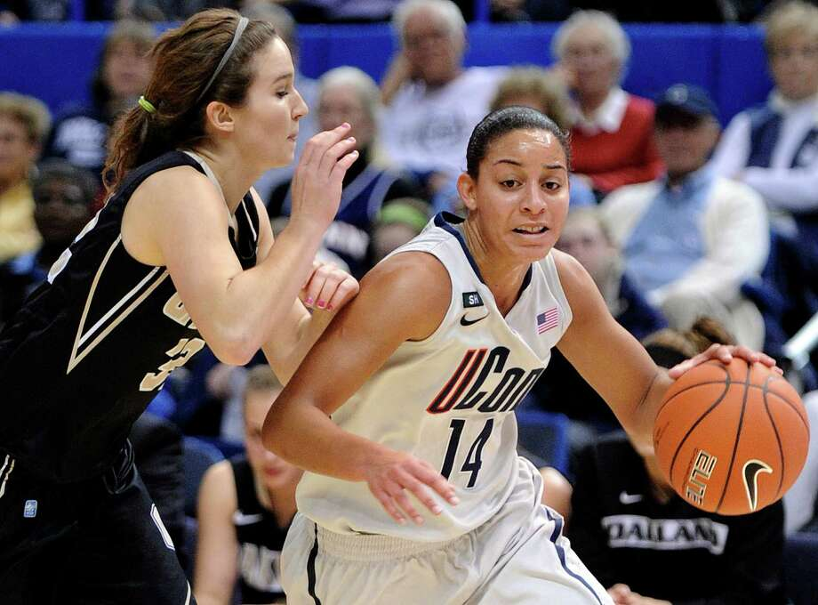 Connecticut's Bria Hartley, right, drives past Oakland's Amy Carleton during the first half of an NCAA college basketball game in Hartford, Conn., Wednesday, Dec. 19, 2012. (AP Photo/Fred Beckham) Photo: Fred Beckham, Associated Press / FR153656 AP