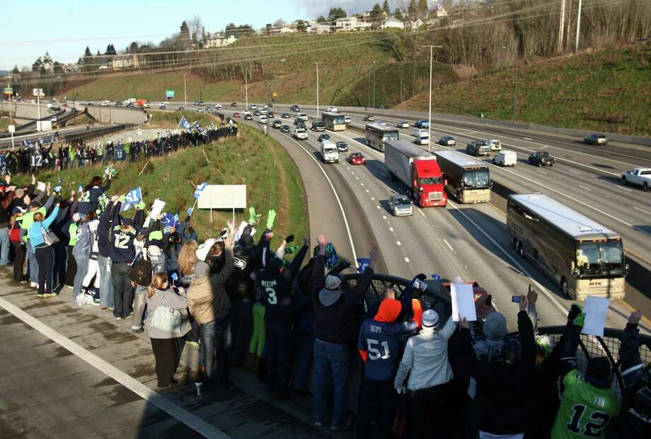 As the team's busses (background) approach, hundreds of Seahawks fans erupt in cheers during a sendoff rally for the Seattle Seahawks in Renton on Friday, January 11, 2013. A crowd of hundreds gathered on an Interstate 405 overpass and cheered the team as their buses headed to the airport for the trip to Atlanta and Sunday's playoff game. Photo: JOSHUA TRUJILLO / SEATTLEPI.COM