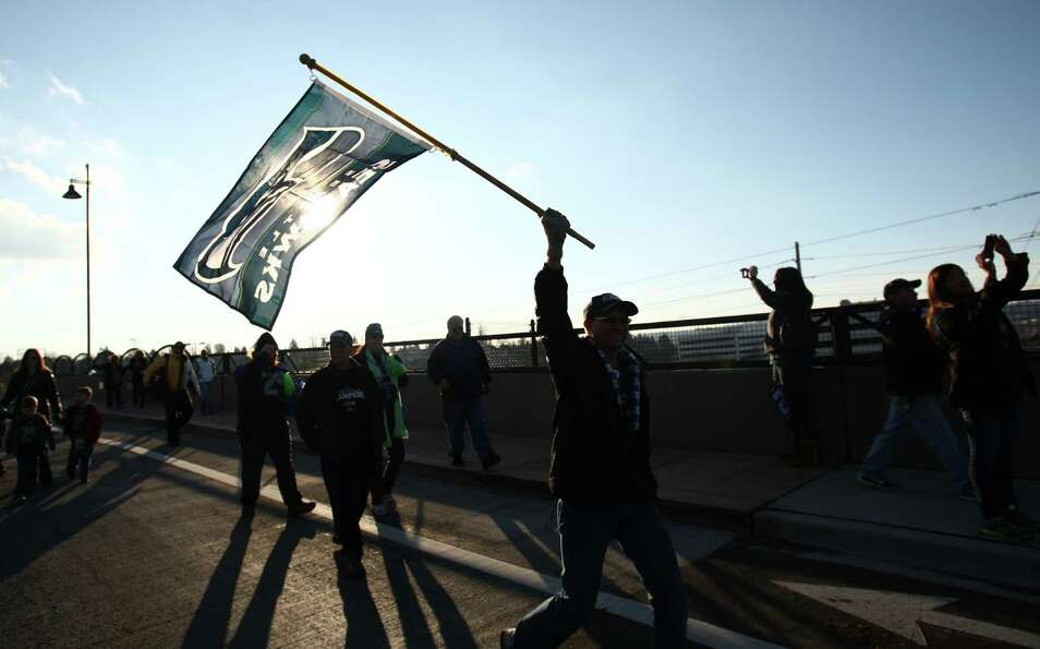 Seahawks fans cheer from the Benson Road overpass on Interstate 405 during a sendoff rally for the S