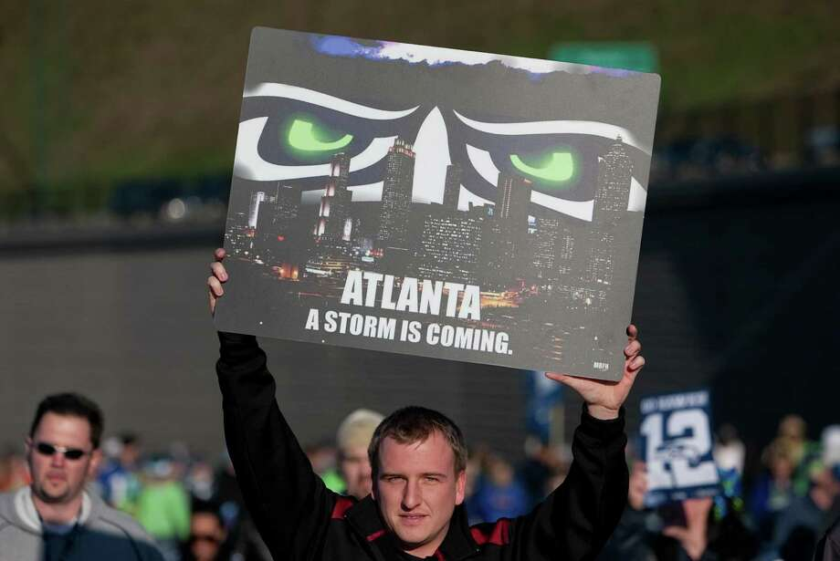A Seahawks fans holds up a poster during a sendoff rally for the Seattle Seahawks in Renton on Friday, January 11, 2013. A crowd of hundreds gathered on an Interstate 405 overpass and cheered the team as their buses headed to the airport for the trip to Atlanta and Sunday's playoff game. Photo: JOSHUA TRUJILLO / SEATTLEPI.COM