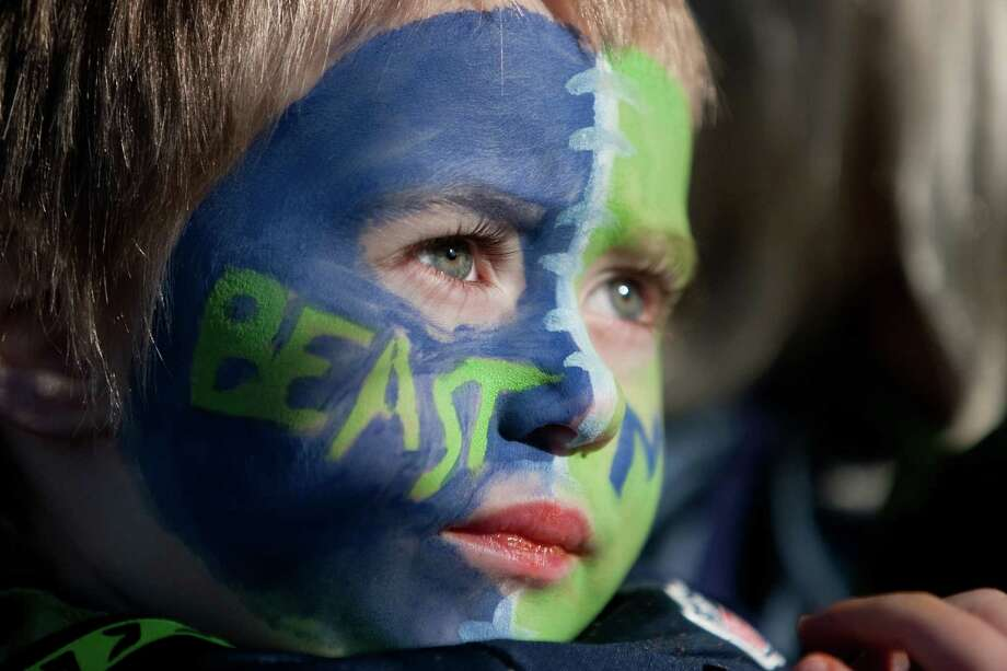Kelly Zinter-Miller, 3, show his spirit during a sendoff rally for the Seattle Seahawks in Renton on Friday, January 11, 2013. A crowd of hundreds gathered on an Interstate 405 overpass and cheered the team as their buses headed to the airport for the trip to Atlanta and Sunday's playoff game. Photo: JOSHUA TRUJILLO / SEATTLEPI.COM