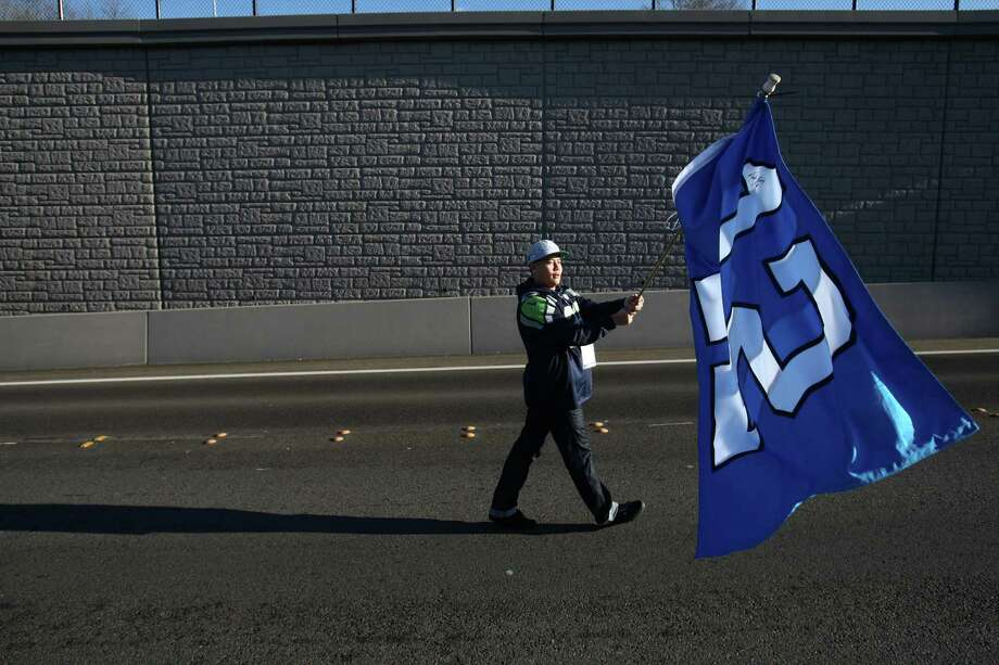 A Seahawks fan marches to a rally during a sendoff rally for the Seattle Seahawks in Renton on Friday, January 11, 2013. A crowd of hundreds gathered on an Interstate 405 overpass and cheered the team as their buses headed to the airport for the trip to Atlanta and Sunday's playoff game. Photo: JOSHUA TRUJILLO / SEATTLEPI.COM