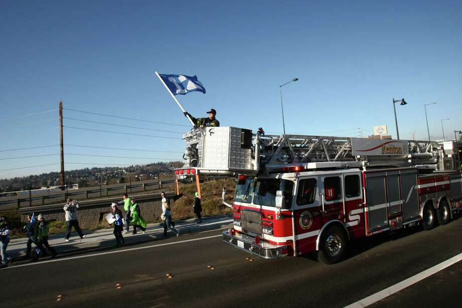 Renton firefighters lead a march during a sendoff rally for the Seattle Seahawks in Renton on Friday, January 11, 2013. A crowd of hundreds gathered on an Interstate 405 overpass and cheered the team as their buses headed to the airport for the trip to Atlanta and Sunday's playoff game. Photo: JOSHUA TRUJILLO / SEATTLEPI.COM