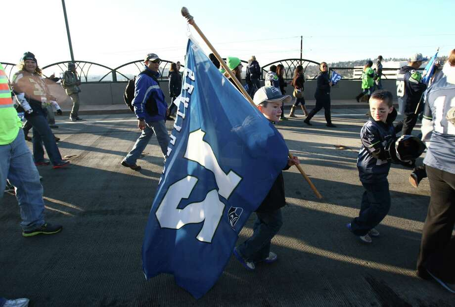 Seahawks fans march during a sendoff rally for the Seattle Seahawks in Renton on Friday, January 11, 2013. A crowd of hundreds gathered on an Interstate 405 overpass and cheered the team as their buses headed to the airport for the trip to Atlanta and Sunday's playoff game. Photo: JOSHUA TRUJILLO / SEATTLEPI.COM