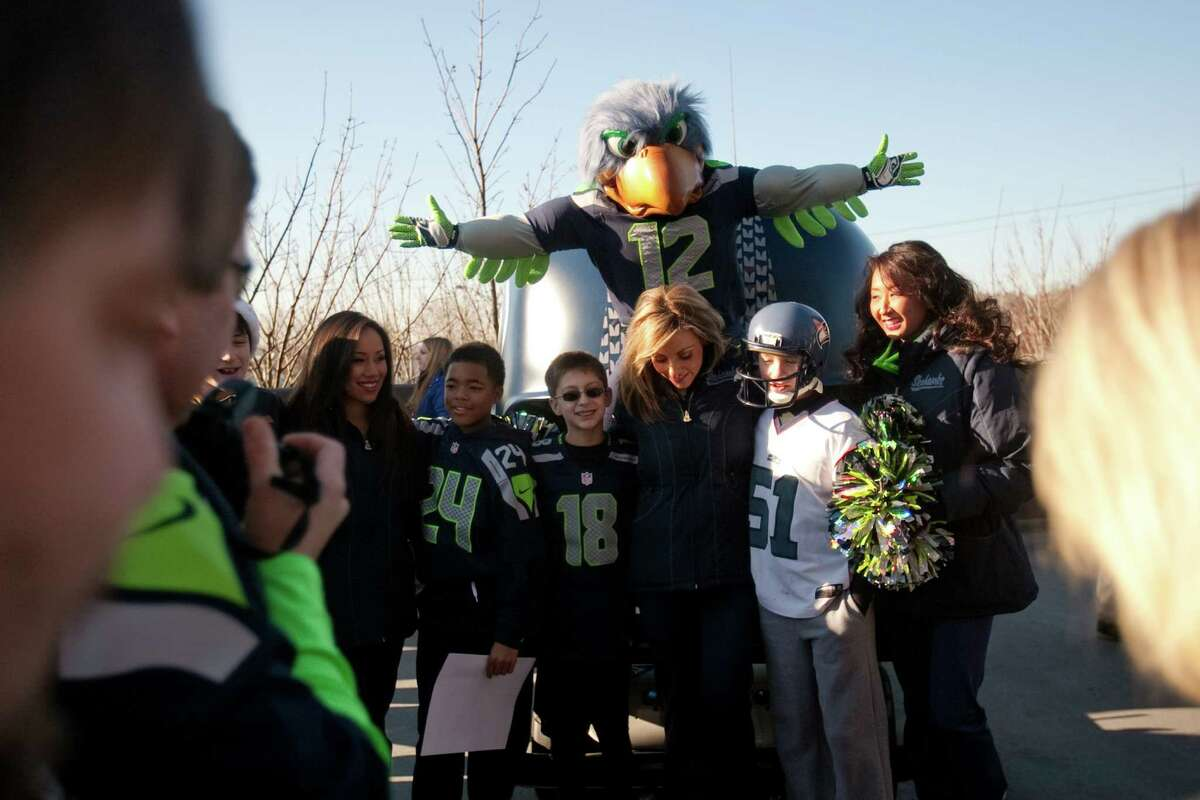 Seahawks mascot Blitz and members of the Sea Gals pose with fans during a sendoff rally for the Seattle Seahawks in Renton on Friday, January 11, 2013. A crowd of hundreds gathered on an Interstate 405 overpass and cheered the team as their buses headed to the airport for the trip to Atlanta and Sunday's playoff game.