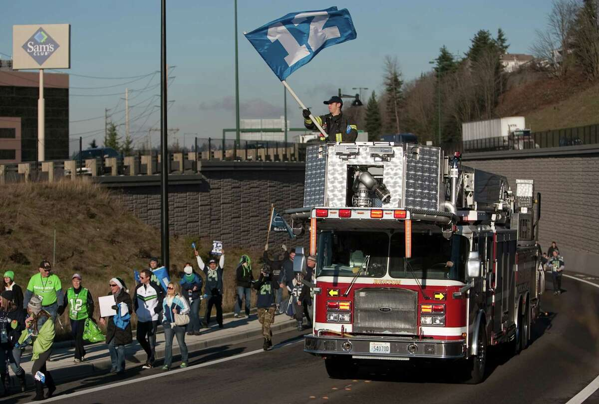 Renton firefighters lead a march of fans during a sendoff rally for the Seattle Seahawks in Renton on Friday, January 11, 2013. A crowd of hundreds gathered on an Interstate 405 overpass and cheered the team as their buses headed to the airport for the trip to Atlanta and Sunday's playoff game.