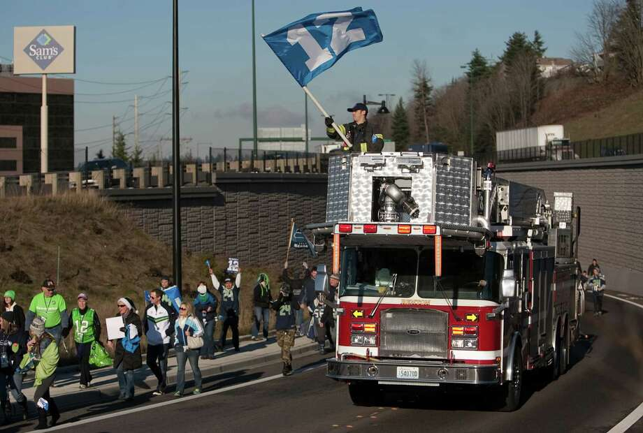 Renton firefighters lead a march of fans during a sendoff rally for the Seattle Seahawks in Renton on Friday, January 11, 2013. A crowd of hundreds gathered on an Interstate 405 overpass and cheered the team as their buses headed to the airport for the trip to Atlanta and Sunday's playoff game. Photo: JOSHUA TRUJILLO / SEATTLEPI.COM