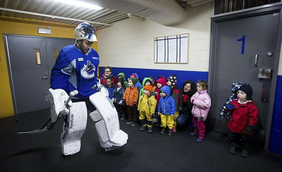 Vancouver Canucks goalie Roberto Luongo walks past a group of children from a daycare who came to watch the team's informal hockey practice at the University of British Columbia in Vancouver, British Columbia, on Friday, Jan. 11, 2013. (AP Photo/The Canadian Press, Darryl Dyck) Photo: Darryl Dyck, Associated Press