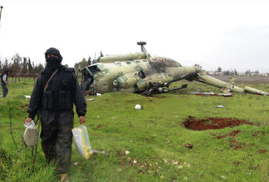 This citizen journalism image provided by Edlib News Network, ENN, which has been authenticated based on its contents and other AP reporting, shows a Syrian rebel carrying food supplies, as he walks in front of a  damaged helicopter at Taftanaz air base that was captured by the rebels, in Idlib province, northern Syria, Friday Jan. 11, 2013. Islamic militants seeking to topple President Bashar Assad took full control of a strategic northwestern air base Friday in a significant blow to government forces, seizing helicopters, tanks and multiple rocket launchers, activists said. (AP Photo/Edlib News Network ENN) Photo: Anonymous
